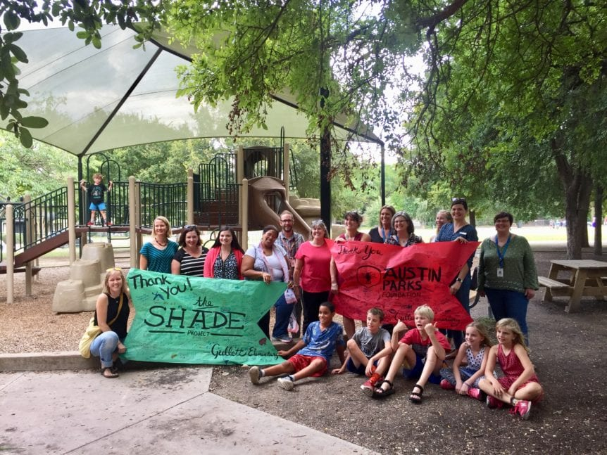 Group under new shade structure at Gullett School Park with a thank you banner