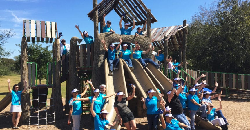 St. David's Foundation staff gather near the new playscape at dove springs park