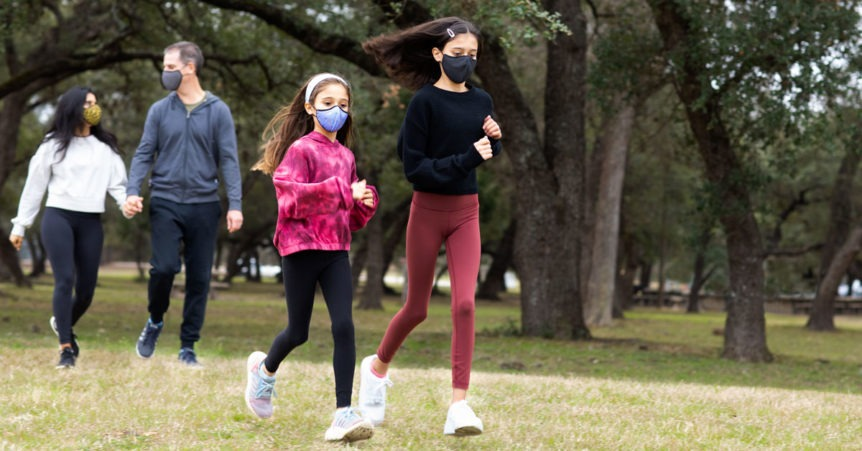 family social distancing in the park with masks