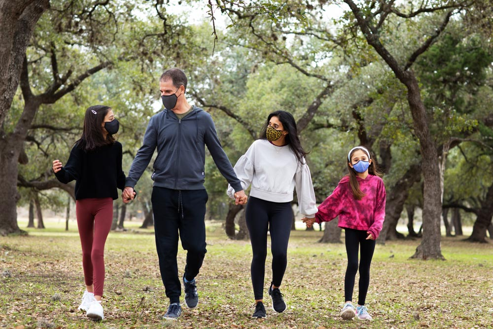 family holding hands at park wearing masks